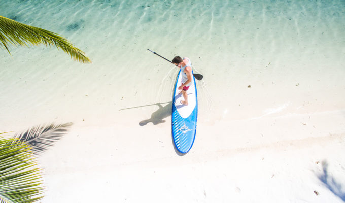 Man getting ready to surf on an inflatable stand up paddle board