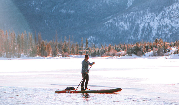 Person stand up paddle boarding on a frozen lake in the mountains